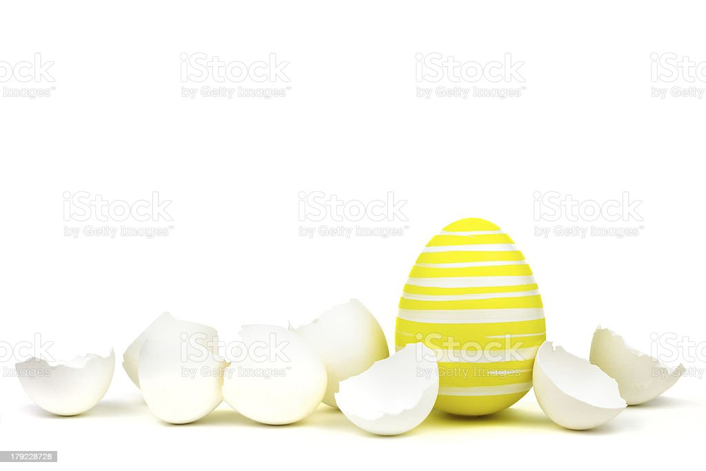 Single yellow easter egg between shells isolated on white royalty-free stock photo