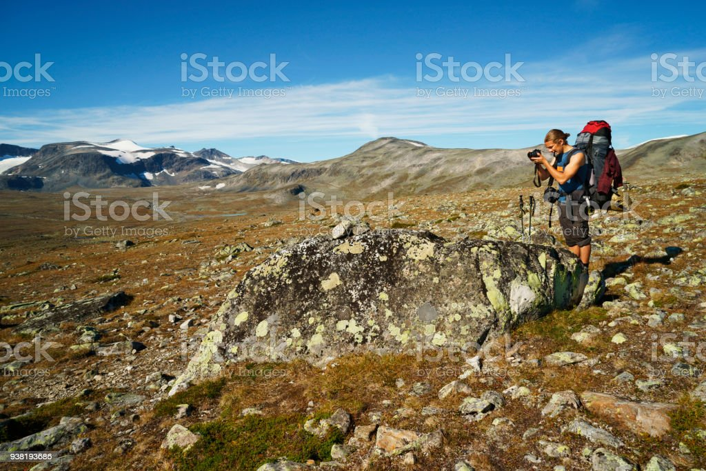 single young man with backpack photographing at scenic mountain landscape of Jotunheimen national park stock photo