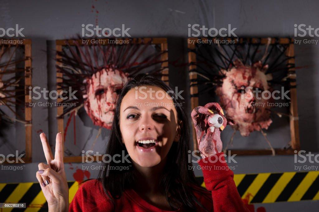 Seule jeune femme étrange montrant paix et tenant le globe oculaire - Photo