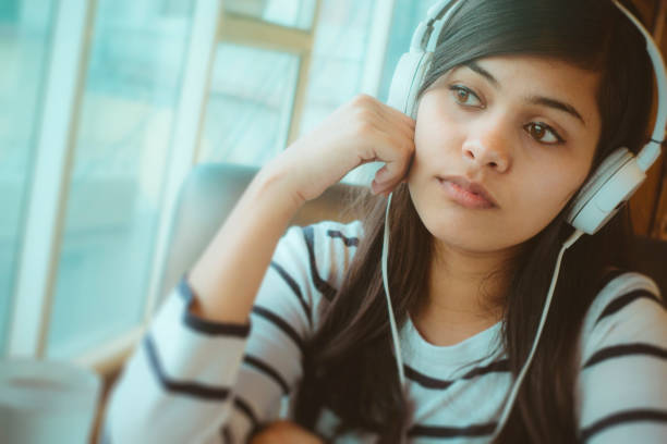 Single young woman listening podcast. stock photo