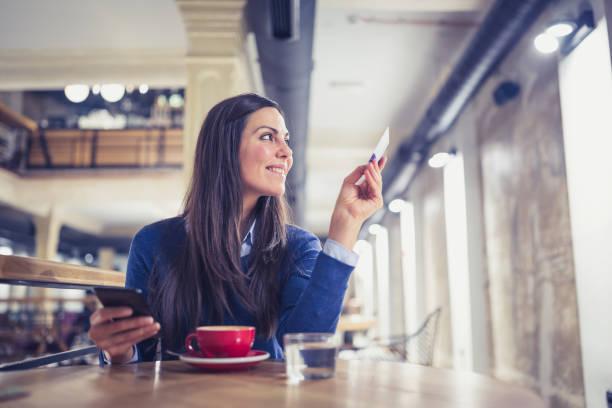 Solo. Mujeres jóvenes en café, de compras en línea pagando con tarjeta - foto de stock