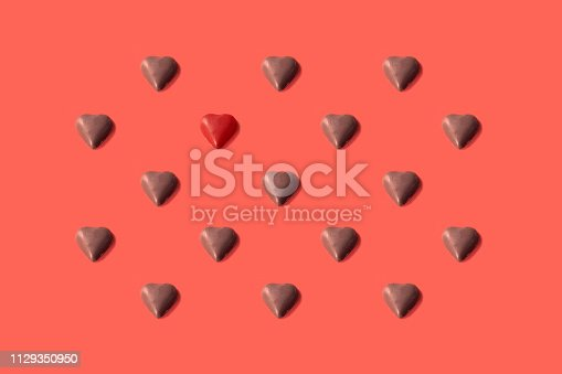 Heart shaped chocolate placed in a repetitive pattern on a Pantone living coral of the year 2019 background