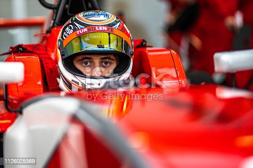 Portrait of a race car driver with a raised visor in his formula car looking at the camera.