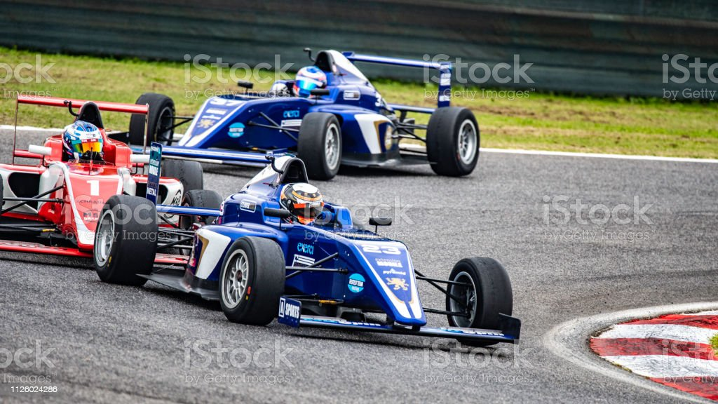 Three formula race cars driving into a corner on a race track.