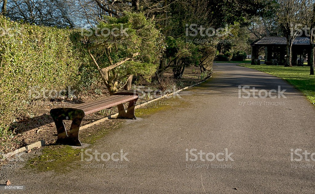 Singular Bench on a park path stock photo