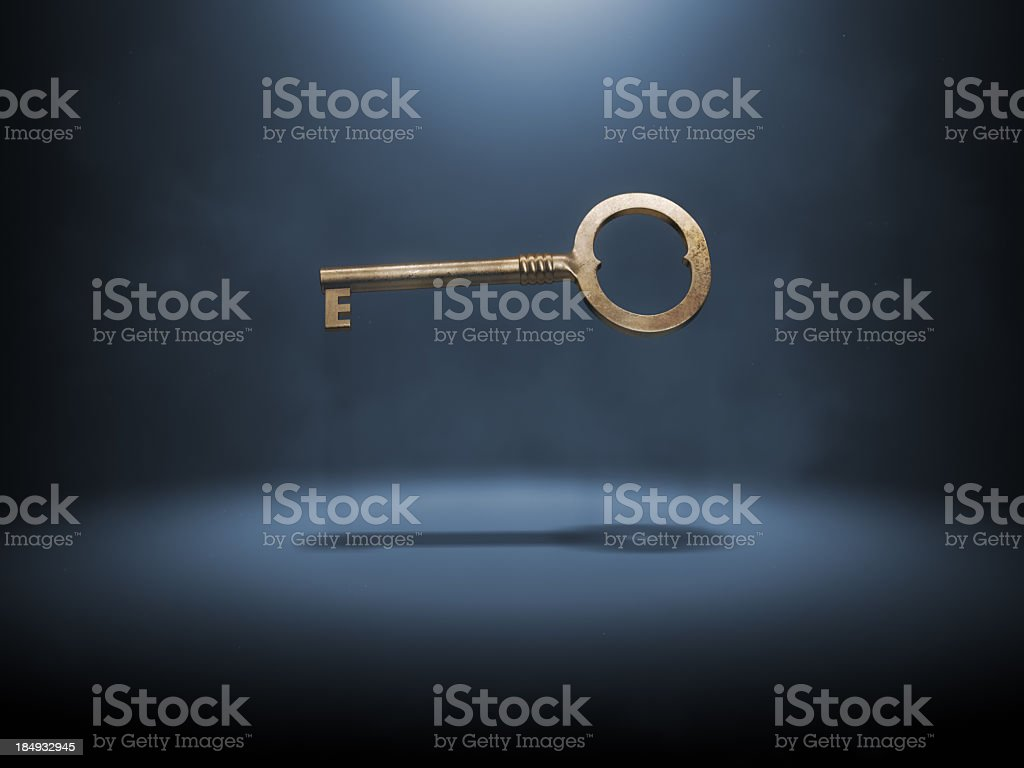 A singular gold key suspended in the air stock photo