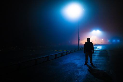 Moody dark image depicting a strange sinister man back lit by street lamps in an abandoned parking lot.