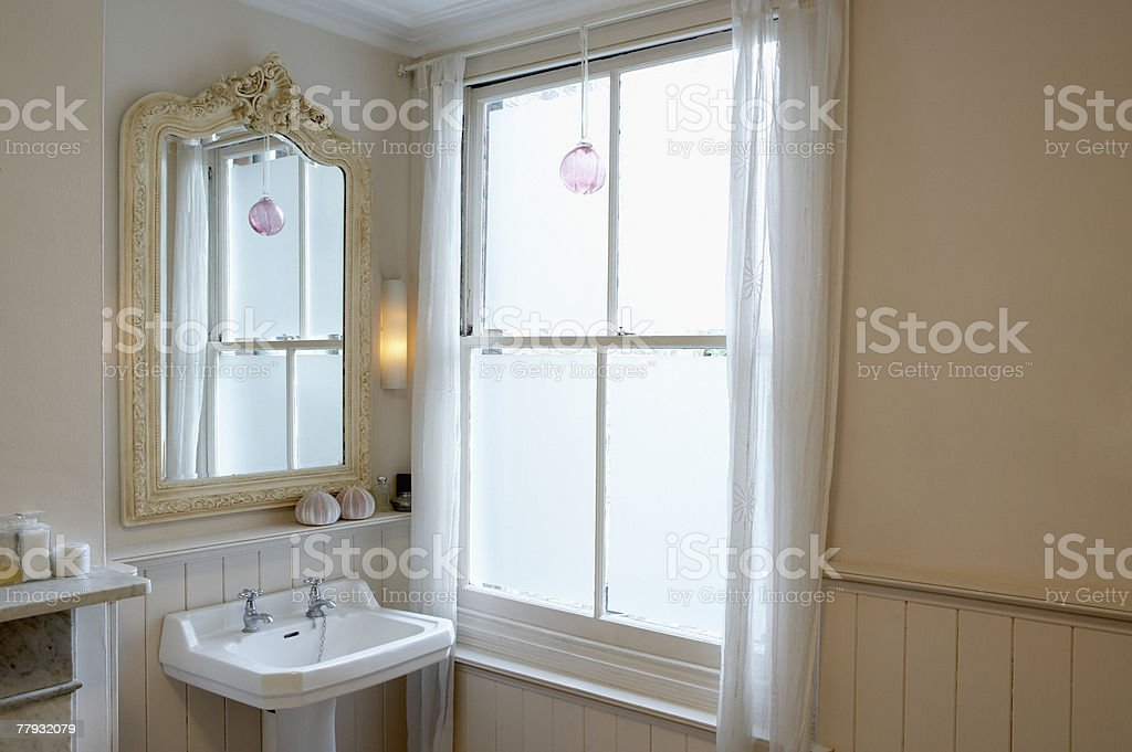 Sink and mirror beside window stock photo