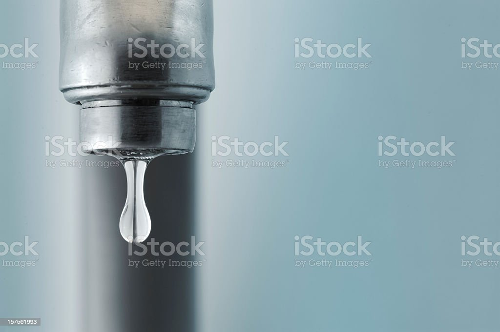 Sink faucet dripping with the water drop in focus stock photo