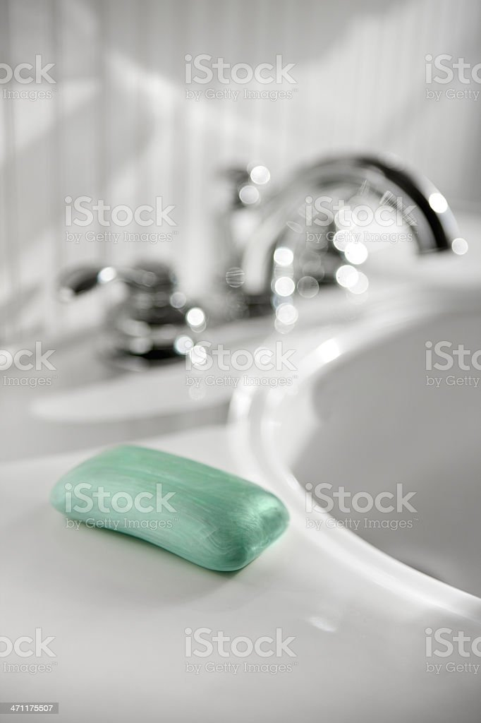 A sink in a white bathroom with a fresh bar of green soap royalty-free stock photo