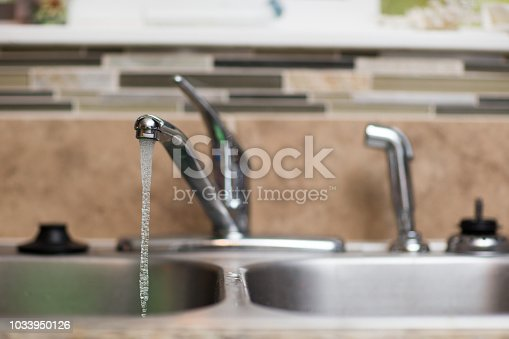Shallow depth of field view of a kitchen sink with the water running