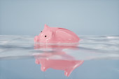 Sinking piggy bank in the water.