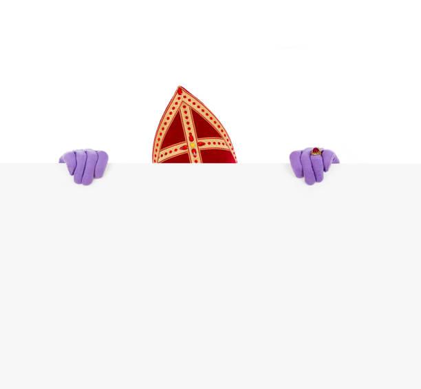 Sinterklaas holding blank cardboard Sinterklaas or saint Nicholas hiding behind blank cardboard. isolated on white background. Dutch character of Santa Claus sinterklaas stock pictures, royalty-free photos & images