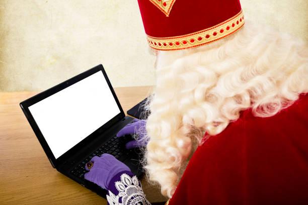 Sinterklaas with notebook or laptop Sinterklaas with notebook. Dutch character of Santa Claus sinterklaas stock pictures, royalty-free photos & images
