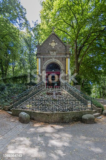 Sint-Rosakapel Chapel dedicated to Saint Rose of Lima patron of the city of Sittard, between two staircases and a cross on the stones with lush trees in the background, South Limburg, Netherlands
