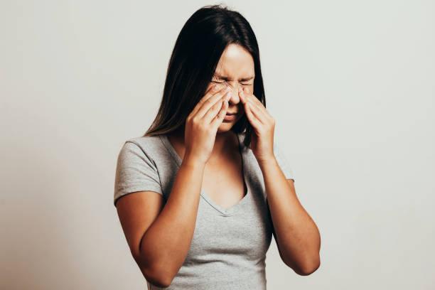 dolor sinusal, presión sinusal, sinusitis. triste mujer le la nariz y la cabeza debido a dolor de seno - física fotografías e imágenes de stock