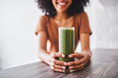 Shot of a young woman enjoying a healthy smoothie at home