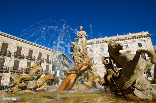Ortygia, Siracusa, Sicily: Fountain of Diana (constructed 1906) with spraying water on Piazza Archimede in Siracusa, Sicily. Backdropped by a bright blue sky.