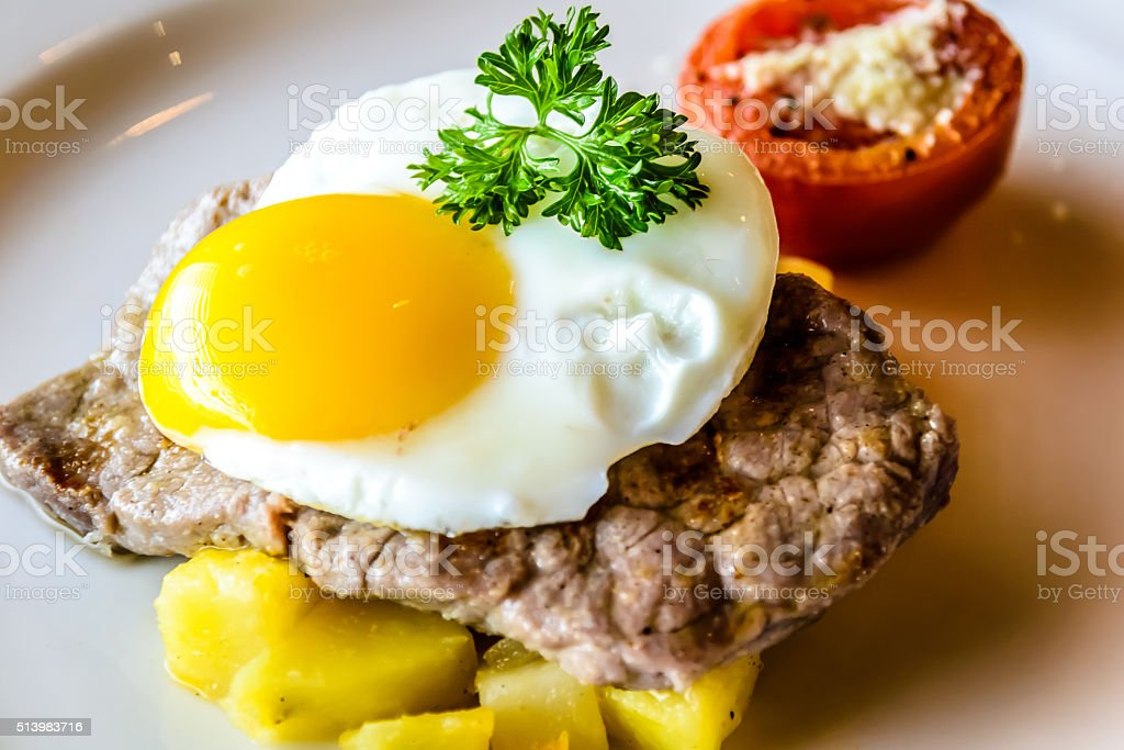 Sirloin steak topped with fried egg and breakfast potatoes stock photo