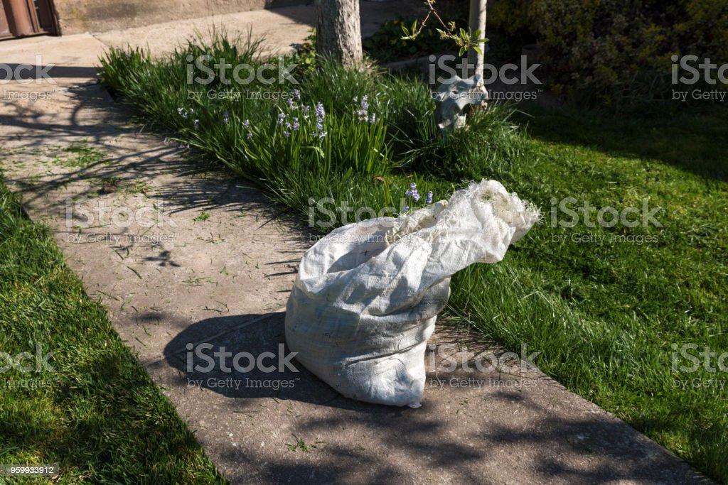 Sisal bag in a garden full of cut grass stock photo