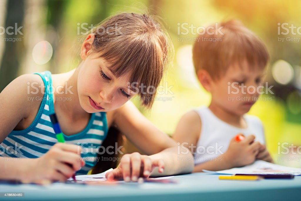 Sister and brother drawing together outdoows stock photo