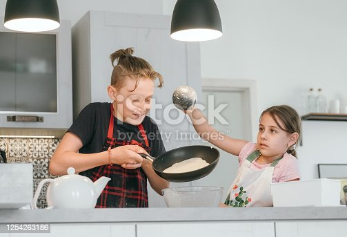 488109116 istock photo Sister and Brother dressed aprons making a homemade pancakes on the home kitchen. Girl poring a liquid dough on the hot pan. Kids Home cooking concept image. 1254263186