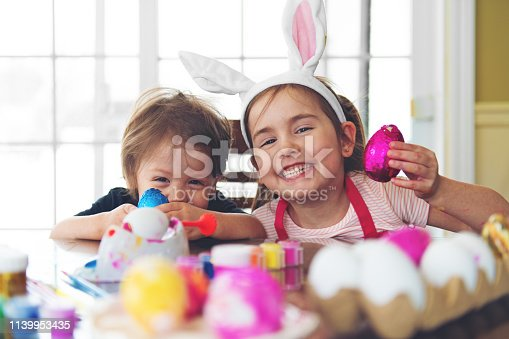 Sister and brother eating chocolate while painting easter eggs