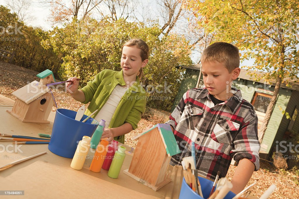 Sister and Brother Painting Colorful Wooden Birdhouses Outdoors in Autumn stock photo