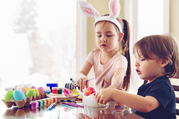 Sister and brother painting Easter eggs stock photo
