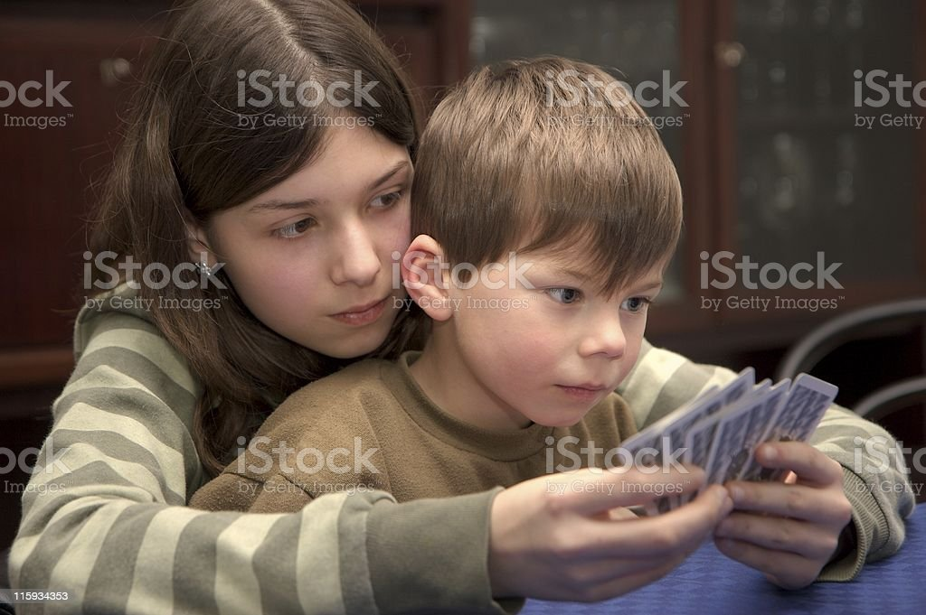 sister and brother playing cards royalty-free stock photo