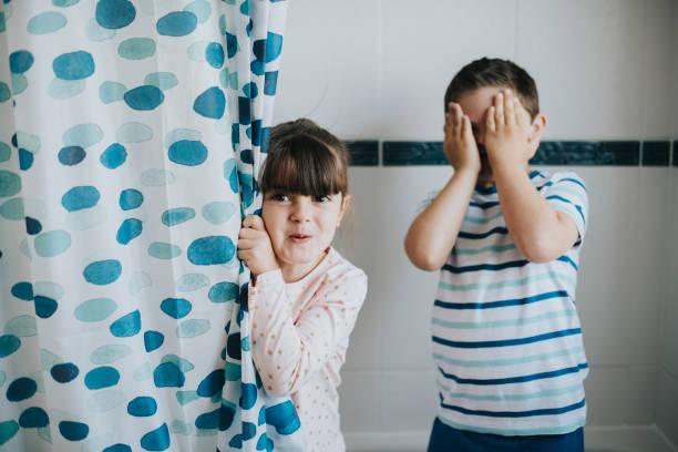 schwester und bruder spielt peekaboo im badezimmer - mädchen dusche stock-fotos und bilder