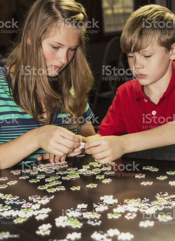 Sister And Brother Teamwork On Jigsaw Puzzle stock photo