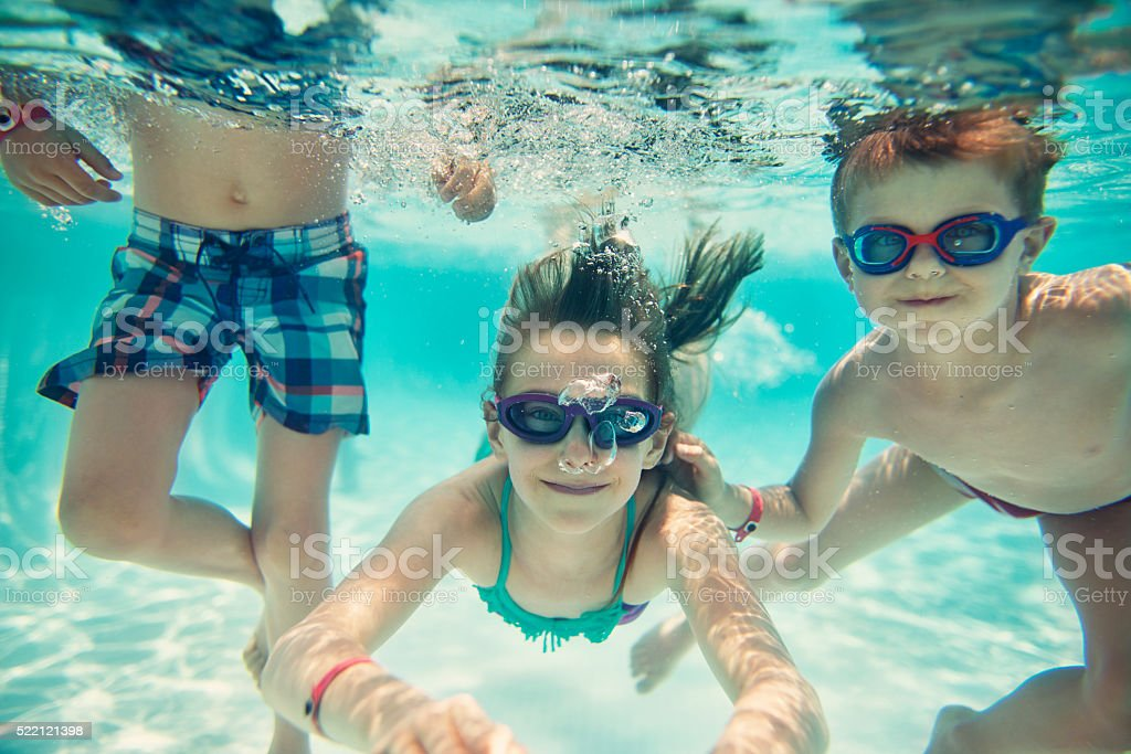 Sister and brothers swimming underwater stock photo