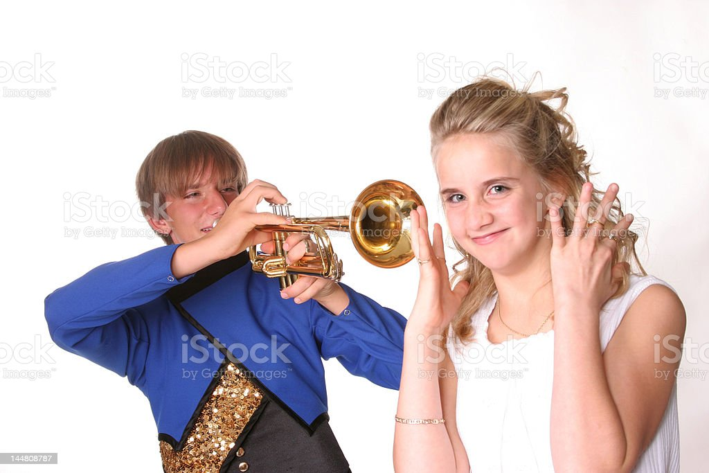 Sister being annoyed by brother with trumpet stock photo