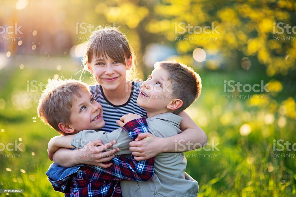 Sister embracing younger brothers in dandelion field stock photo