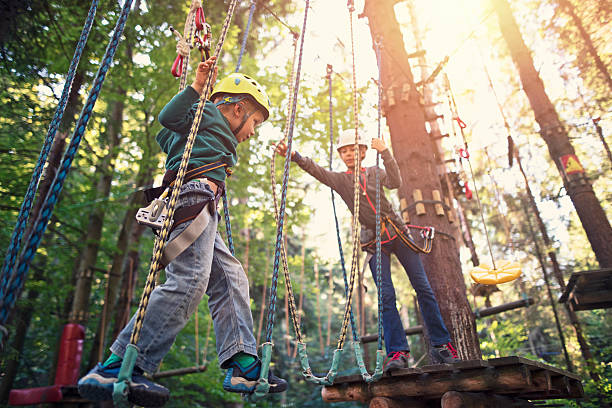 Sister helping her brother during ropes course in adventure park stock photo