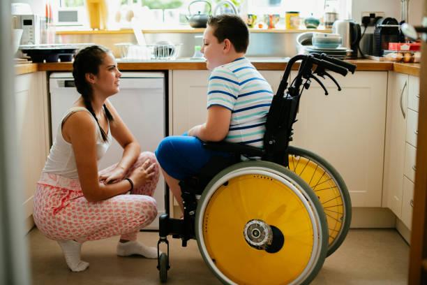 妹は台所で無効になっている弟を助ける - disabilitycollection ストックフォトと画像