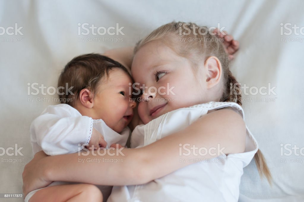 Sister hugs her younger brother stock photo