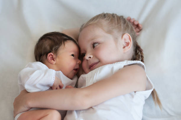 sister hugs her younger brother - sister stock photos and pictures
