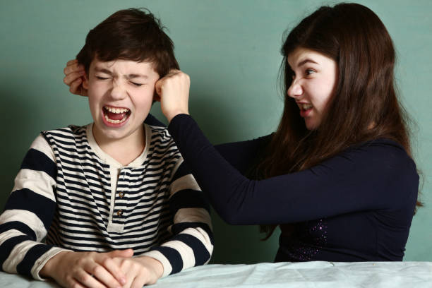 sister pull brother ear as a loss in argument stock photo