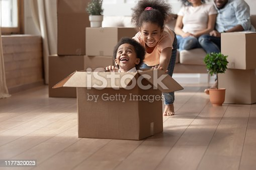 African older sister riding younger cute brother who is sitting in cardboard box, on background big carton boxes stuff and parents sitting on couch enjoy new modern house resting at moving day concept