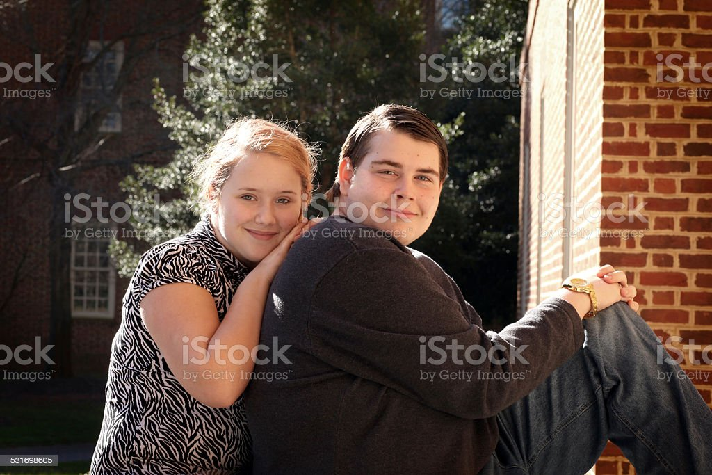Sister showing her Autistic brother some love and affection. stock photo