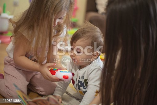 istock Sister showing toy to her brother. 1126210884