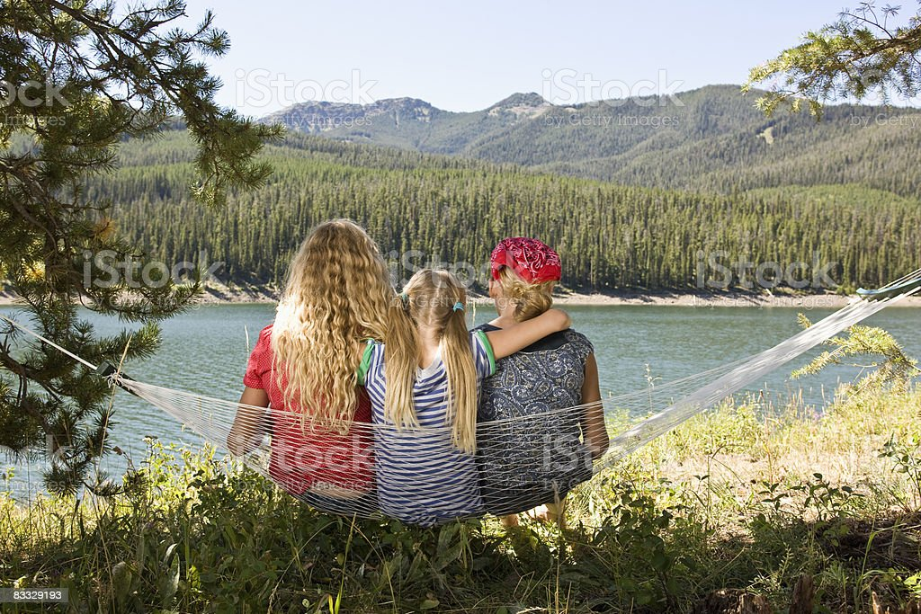 Sister sitting on hammock together by lake royaltyfri bildbanksbilder