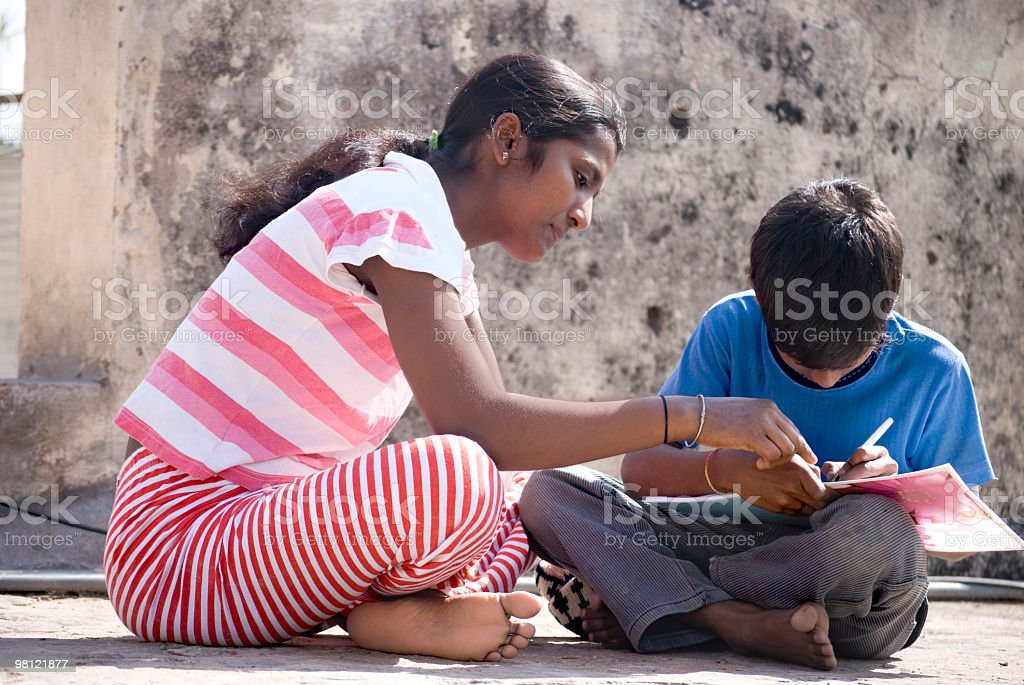 sister teaching her brother how to write royalty-free stock photo