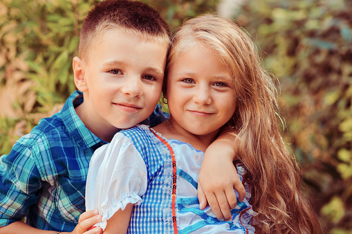Sister with brother shows affection, embraces and smiles isolated nature green shrub tree background