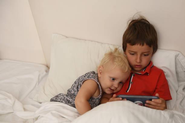 Soeur avec son frère regardant des dessins animés au téléphone. - Photo