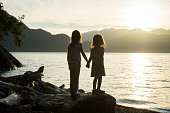 Sisters holding hands at sunset by the sea at Porteau Cove, BC, Canada