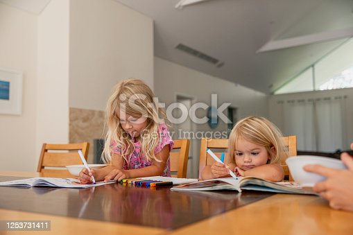 A shot of two young caucasian sisters drawing and colouring in at a table in their home in Perth, Australia.