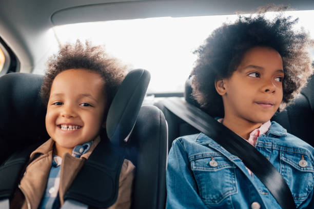 Sisters driving in the back seat of the car stock photo
